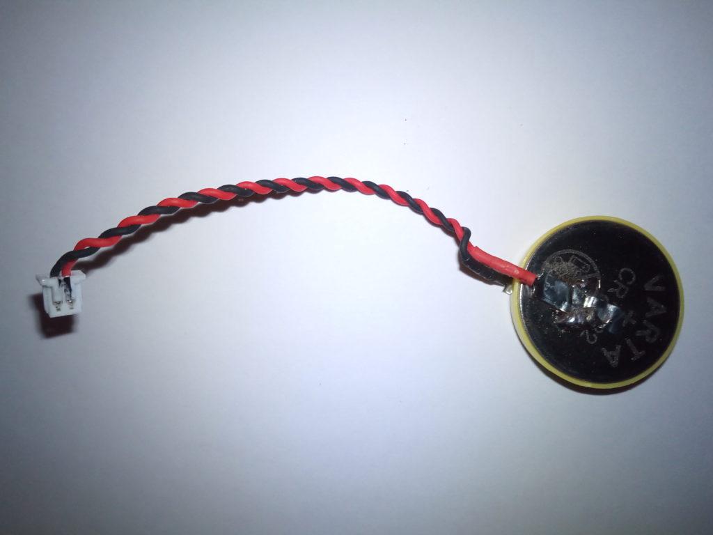 Neue CR2032 Knopfzelle mit Isolationsring an Schweißband gelötet